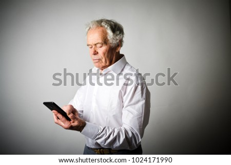 Old man in white is using a smart phone.