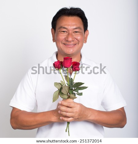 Old man in white t-shirt with bouquet of roses