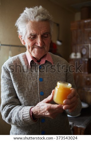 Old man indoor holding happy a jar of honey with pollen - stock photo