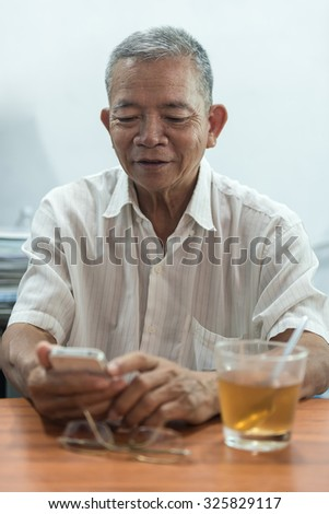Old man is happy when use a smartphone
