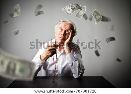 Old man is praying with wooden rosary beads. Falling dollar banknotes. Currency, prayer and mercy concept.