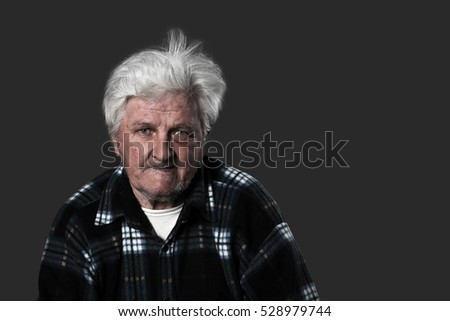 Old man looks serious on dark background with blank copy space for text message
