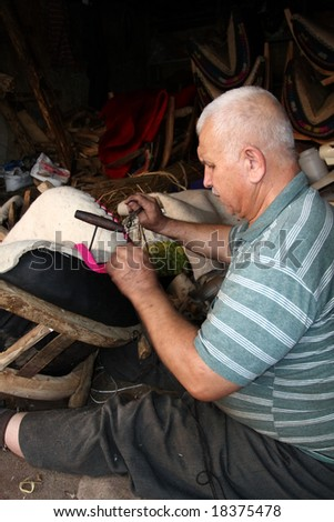 old man making traditional saddle for horses - stock photo