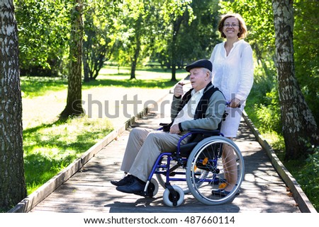 old man on wheelchair and young female medical assistant in the park