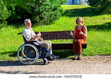 old man on wheelchair and young woman sitting on a bench and showing OK - thumbs up