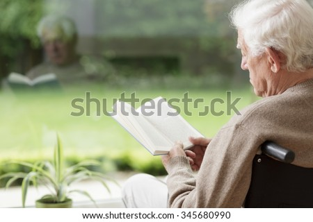 Old man on wheelchair reading a book - stock photo