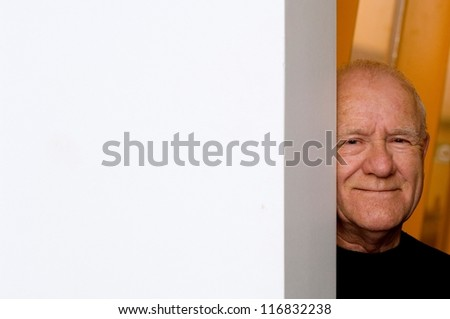Old man peeking from behind a corner - stock photo