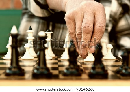 old man playing chess and make the first move - stock photo