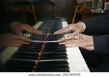 Old Man Playing The Piano with its dilapidated hands - stock photo