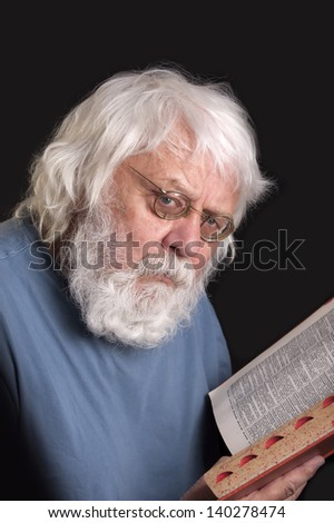 Old man reading a book, scientist and teacher with beard and glasses - stock photo