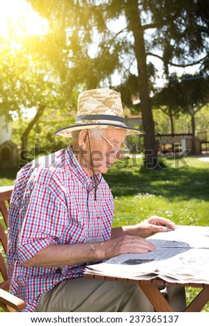 Old man reading newspapers in backyard at table