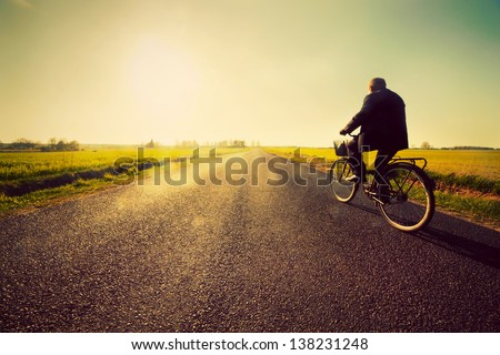 Old man riding a bike on asphalt road towards the sunny sunset sky - stock photo