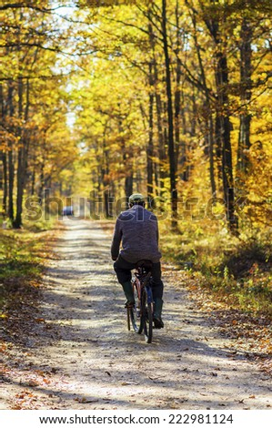 Old man riding a classic bicycle in autumn forest - stock photo