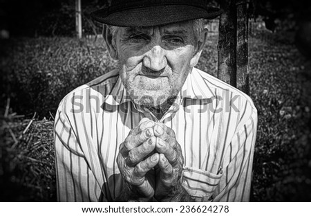 Old man's hands, praying in the yard. Black and white picture. - stock photo
