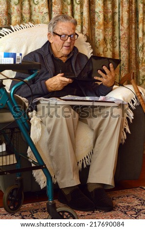 Old man (90s) in eyeglasses working with laptop computer at home. Lifestyle concept technology, oldness, old age, retirement, family.
