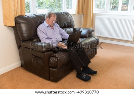 Old man sat on a leather sofa in his lounge wearing slippers and using a laptop