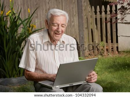Old man senior citizen using laptop computer - stock photo