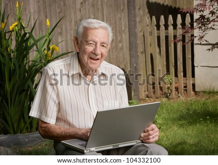 Old man senior citizen with laptop computer - stock photo