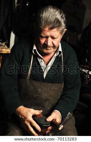 Old man, shoemaker, repairing old handmade shoe in his workshop - stock photo
