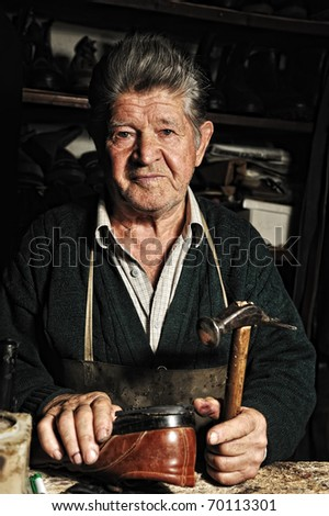 Old man, shoemaker, repairing old handmade shoe in his workshop and looking at the camera - stock photo