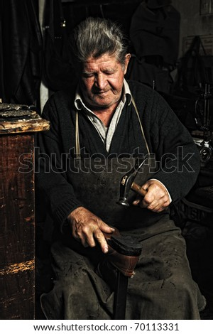 Old man, shoemaker, repairing old handmade shoe in his workshop, hitting with a  hammer - stock photo