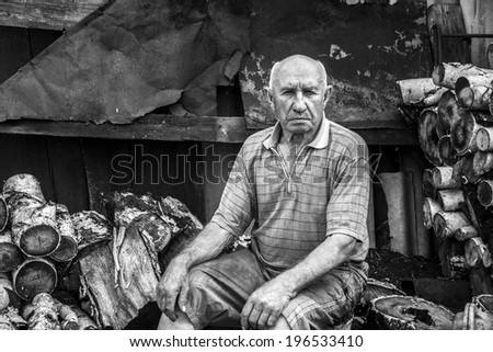 old man sits on the wood background - stock photo
