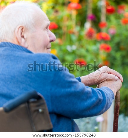 Old man sitting alone in a wheelchair out in the garden. - stock photo