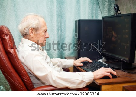 old man sitting in a chair and working with computer - stock photo