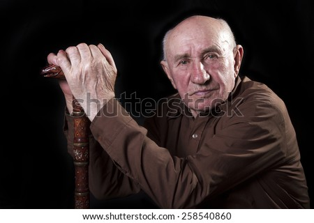old man sitting in the armchair with his walking stick - stock photo