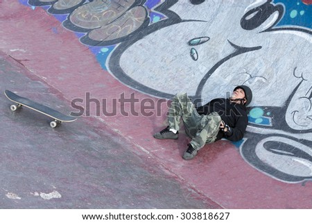 old man skater lying down on the floor is resting on a skating park - focus on the face