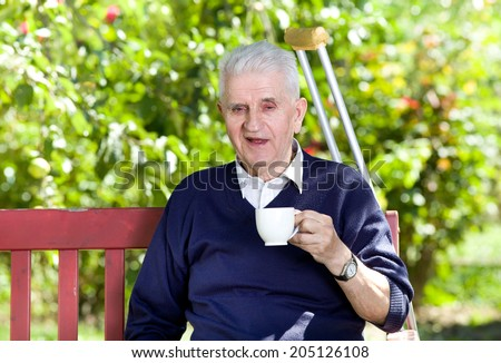 Old man smiling and drinking coffee in garden - stock photo