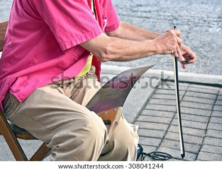 old man street performer playing music with hand saw and bow - stock photo