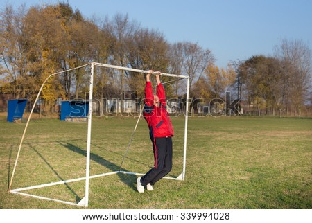 Old man stretching back on the soccer goal at playground - stock photo
