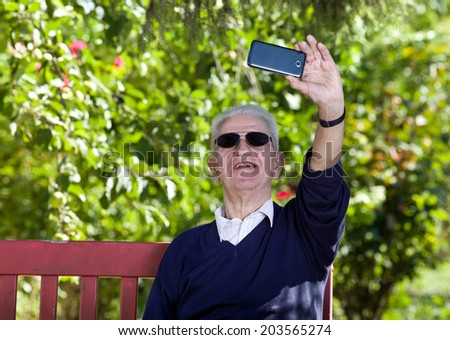 Old man taking a selfie wit cell phone, seated on bench in park  - stock photo