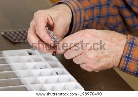 Old man taking out pills from blister into pills box to organize weekly dose - stock photo