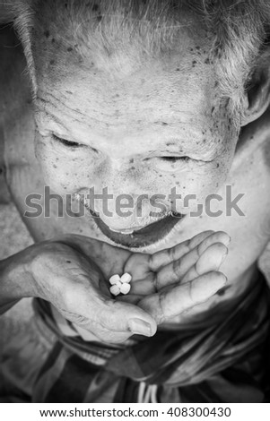 Old man taking tablet ,black and white tone - stock photo