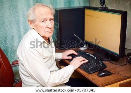 old man typing something on his computer - stock photo