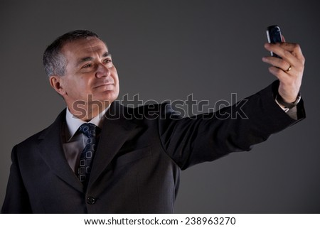 old man using a smartphone on a neutral background