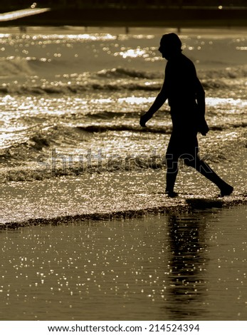 Old man walking by the sea shore