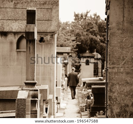 Old man walking in Montparnasse Cemetery in Paris (France). Rear view. Selective focus on the cross and tomb at foreground. Aged photo.  Sepia. - stock photo