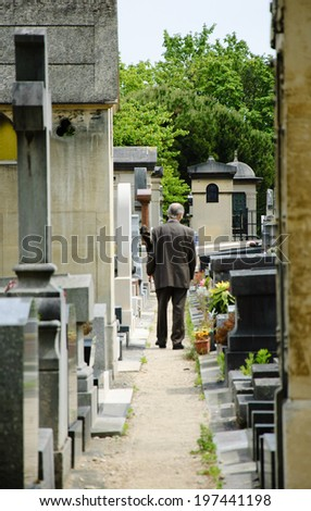 Old man walking in Montparnasse Cemetery in Paris (France). Rear view. Selective focus on the tombs and trees at the backgrounds.  - stock photo