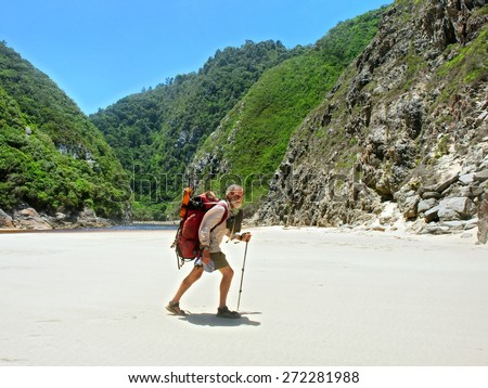 Old man walks on beach with a backpack. Shot on the Otter trail in the Tsitsikamma National Park, Garden Route area, Western Cape, South Africa.  - stock photo