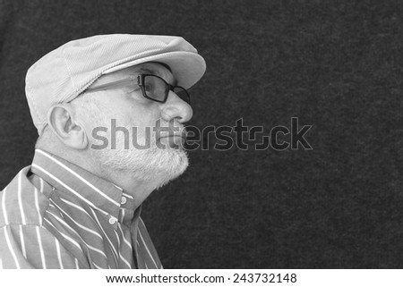 Old Man Wearing a Cap, Spectacles and Striped Shirt - stock photo