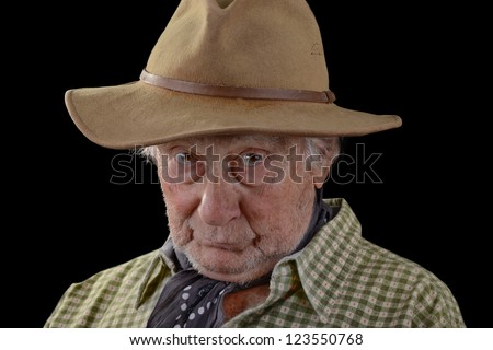 Old man wearing a tan felt hat and a green checked shirt with scarf around neck isolated on black - stock photo