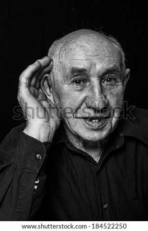 old man who hears evil, hand to ear listens isolated black background