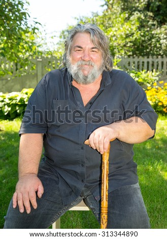 Old man with a grey beard. Senior man in park. Portrait of smiling aged caucasian man with a gray beard on green park background. Happy pensioner. - stock photo