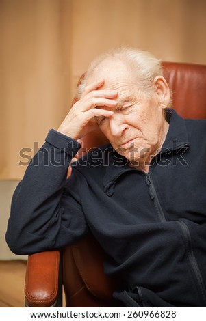 old man with a headache, his hand on his forehead - stock photo