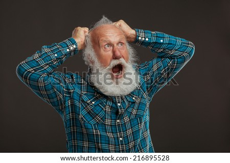 old man with a long beard with big smile on a dark background - stock photo