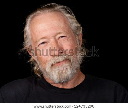 Old man with an amused look on his face isolated against a black back ground - stock photo