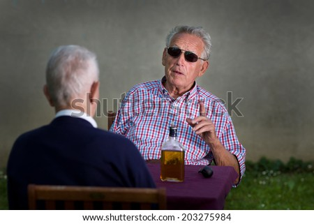 Old man with black sunglasses holding forefinger up and discussing with another old man - stock photo